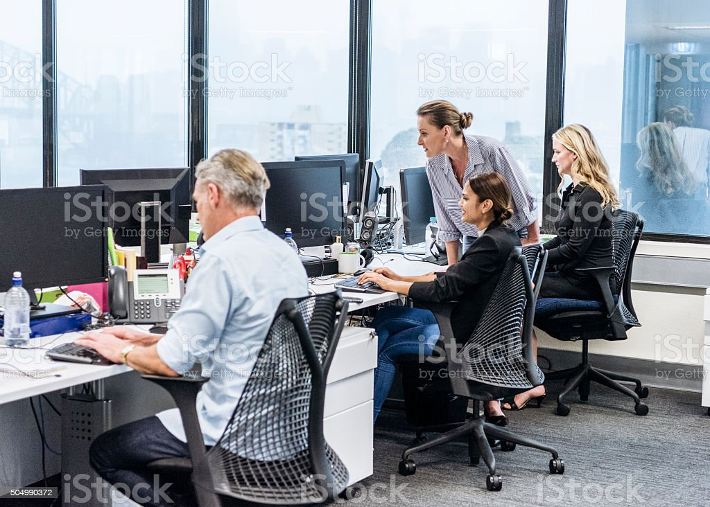 Office workers at desks using computer, female manager with staff stock photo