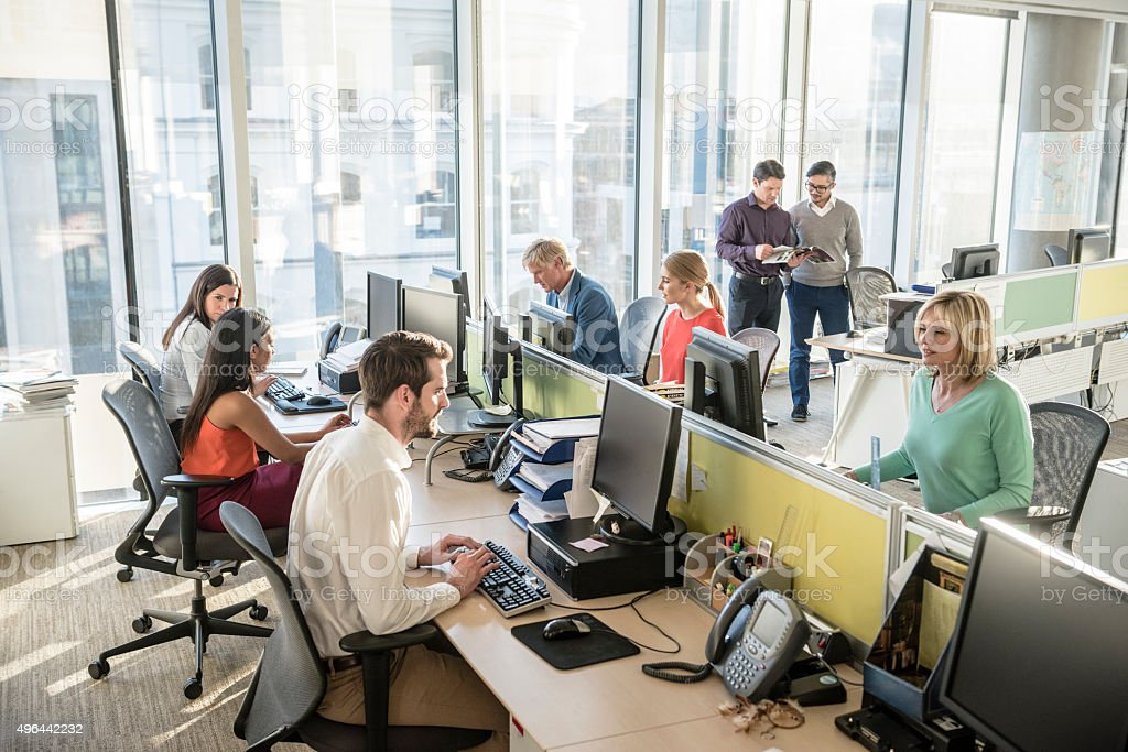 Office workers at desks using computers in modern office stock photo