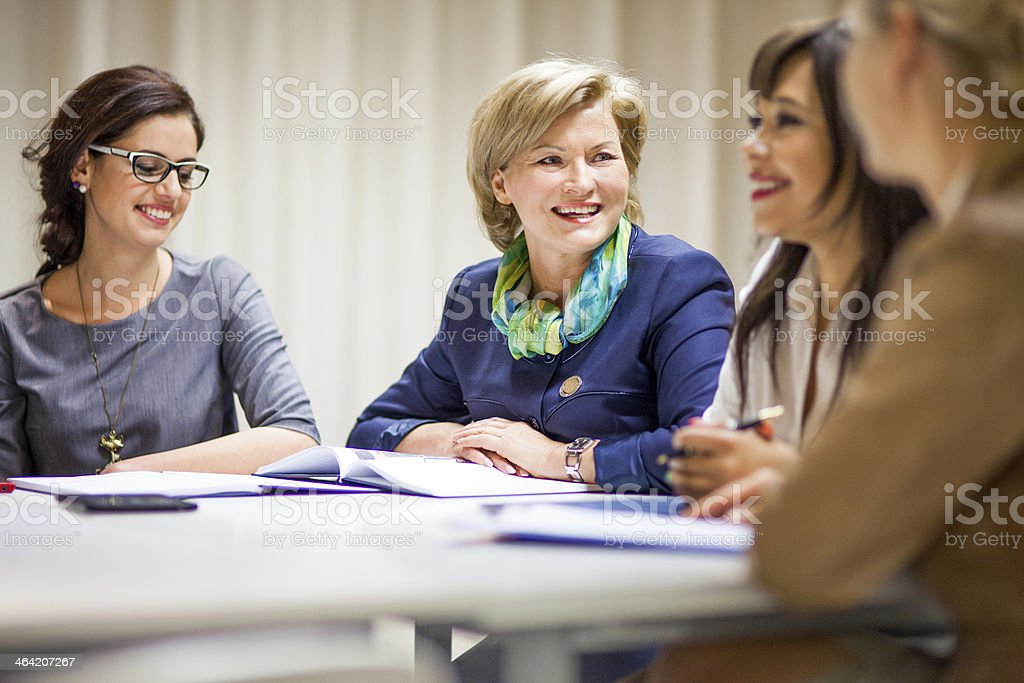 Office workers / businesswomen sitting at a desk stock photo