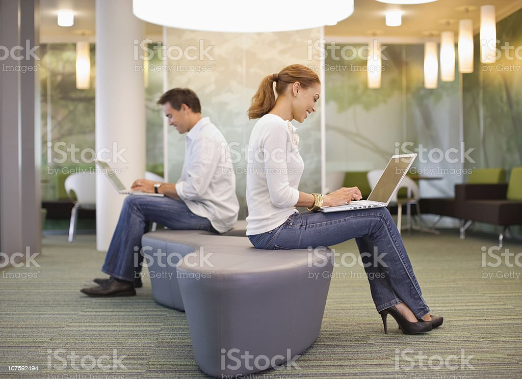 Office workers using laptop back to back at modern office canteen, side view royalty-free stock photo