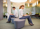 Office workers using laptop back to back at modern office canteen, side view