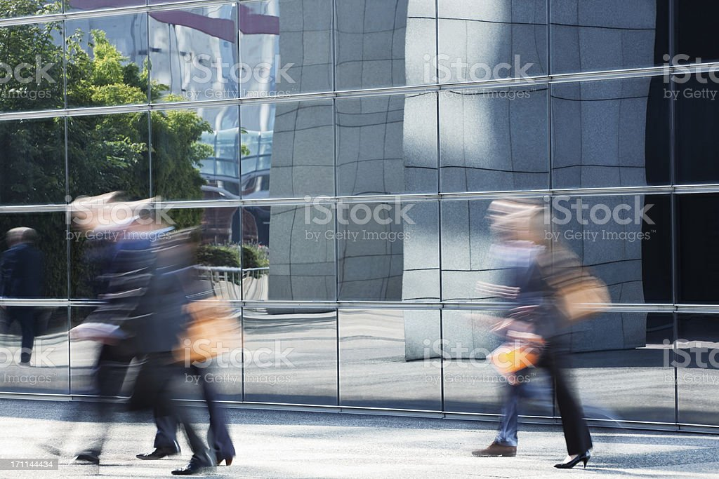 Office Workers Walking Along Glass Building, Blurred Motion royalty-free stock photo