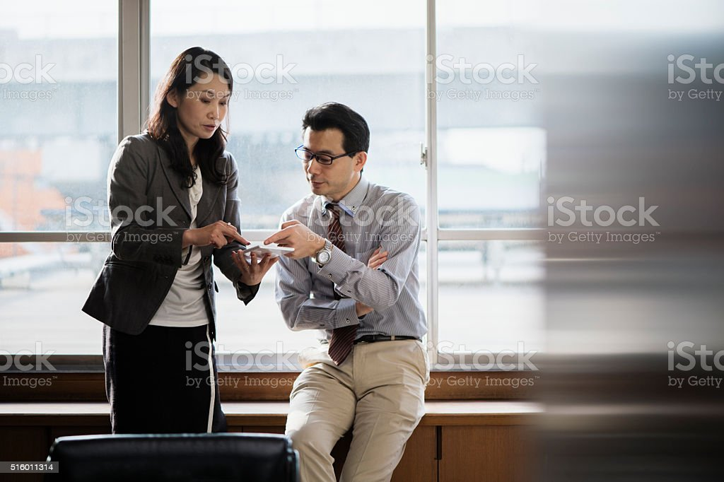 Office workers working together on tablet pc stock photo