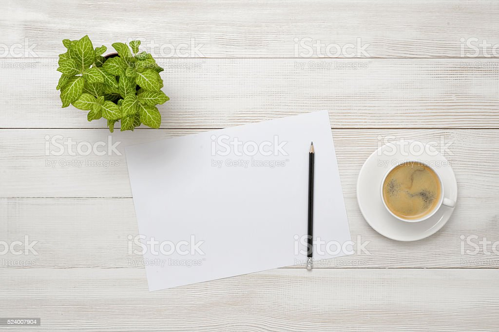 Office workplace with green houseplant, cup of coffee, white paper stock photo