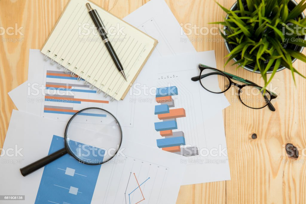Office workplace with Magnifying glass on wood table,supplies and reports for analysis business plan stock photo