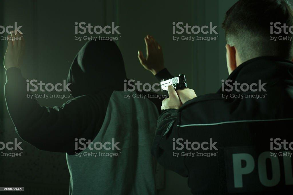 Officer keeping gun on crook stock photo