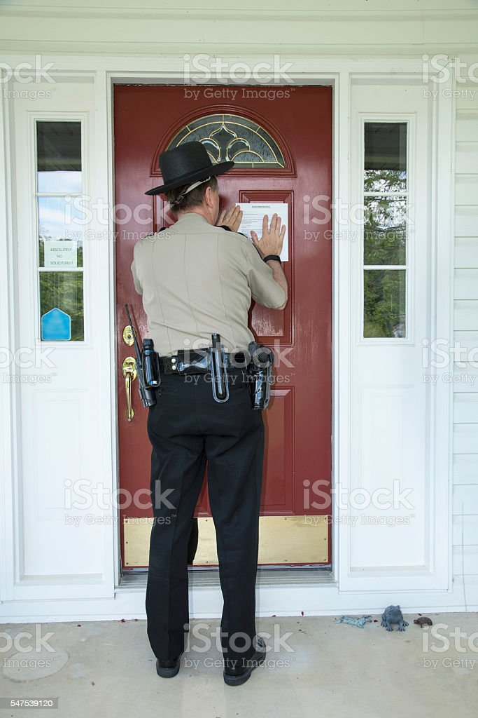 Officer placing an eviction notice stock photo