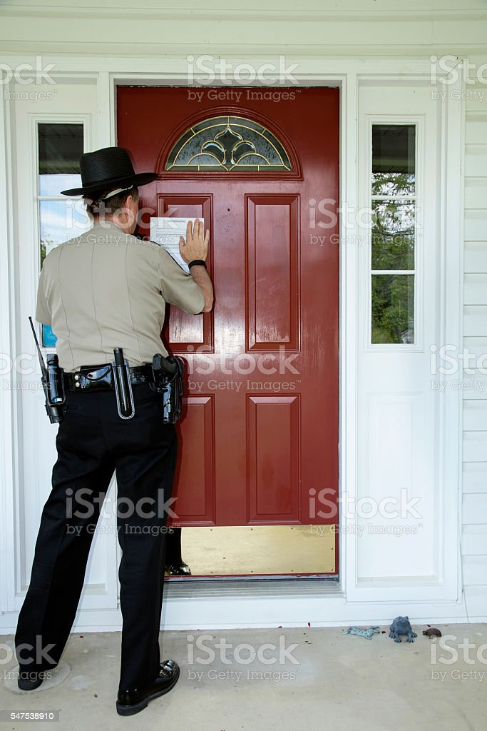 Officer posting an eviction notice stock photo