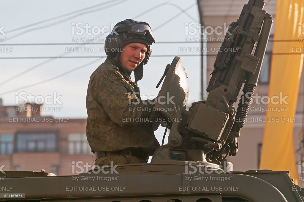 Officer sits in open Msta-S howitzer hatch near anti-aircraft gun stock photo