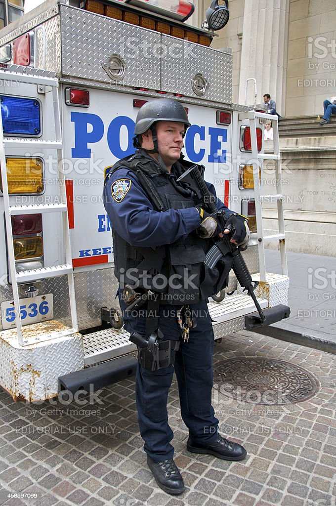 NYPD officer stands watch along Wall Street, NYC, USA royalty-free stock photo