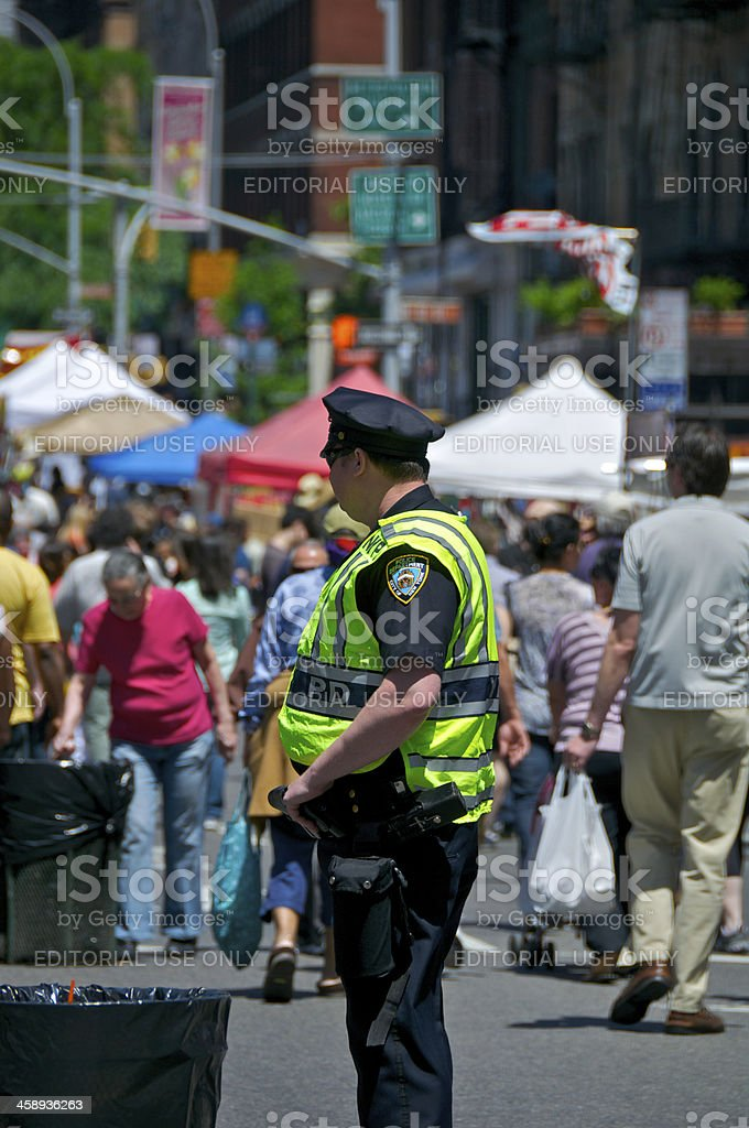 NYPD Officer watches people at street fair, Manhattan, NYC royalty-free stock photo