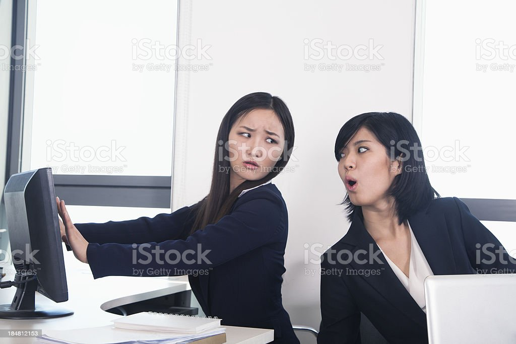 Officer worker hiding her computer from coworker stock photo