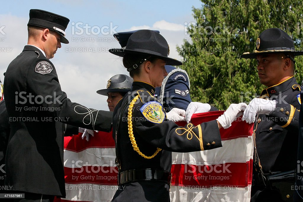 Officers Folding the American Flag at a Memorial Service stock photo