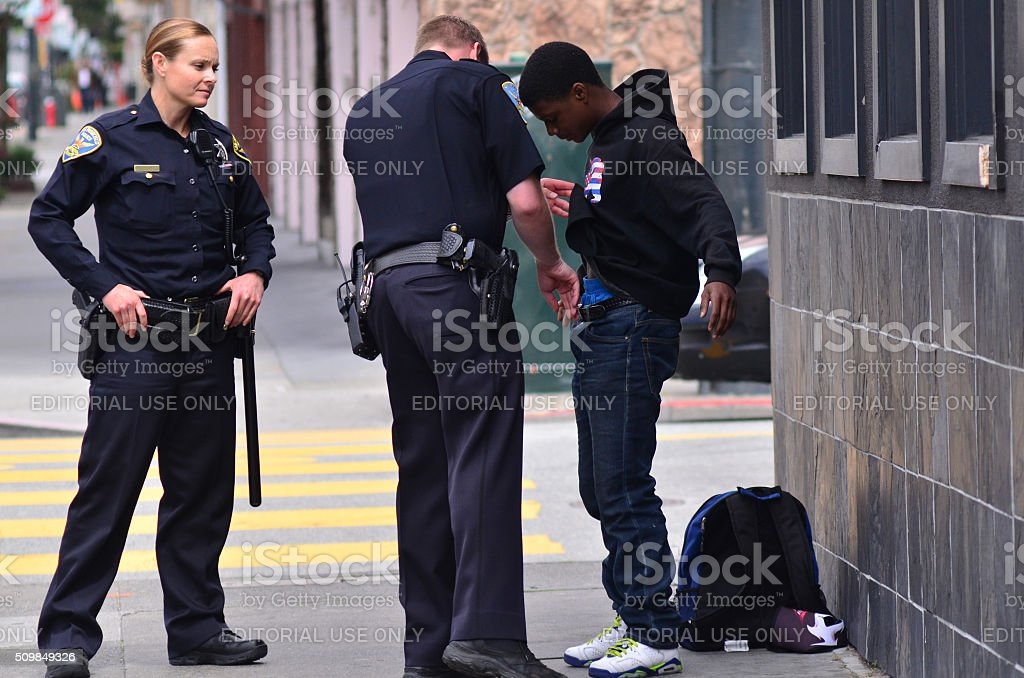 SFPD officers patdown black american man in San Francisco stock photo
