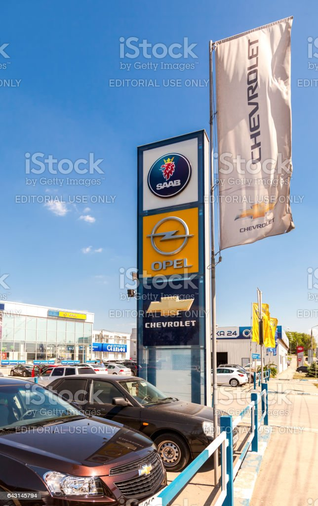 Official dealership signs and flags against blue sky stock photo