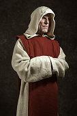 Official portrait of monastic. Studio shot against dark wall.
