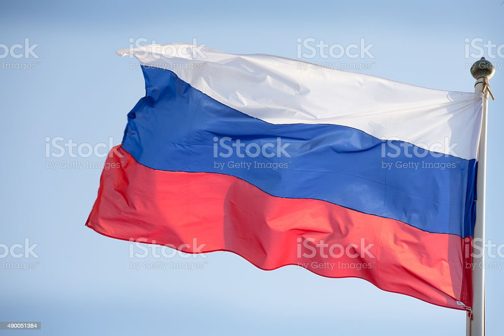 Official russian flag on the blue sky background stock photo