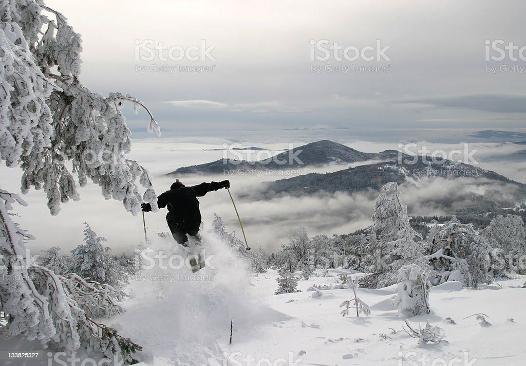 Off-piste skier jumping a bump stock photo