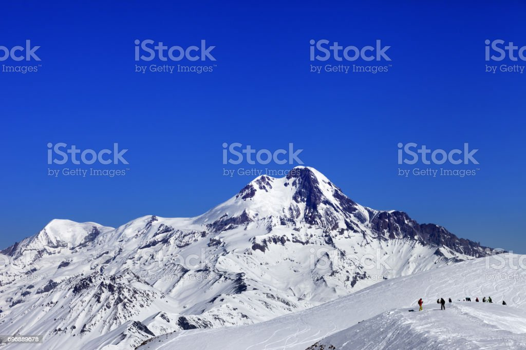 Off-piste slope and mount Kazbek at sun winter day stock photo