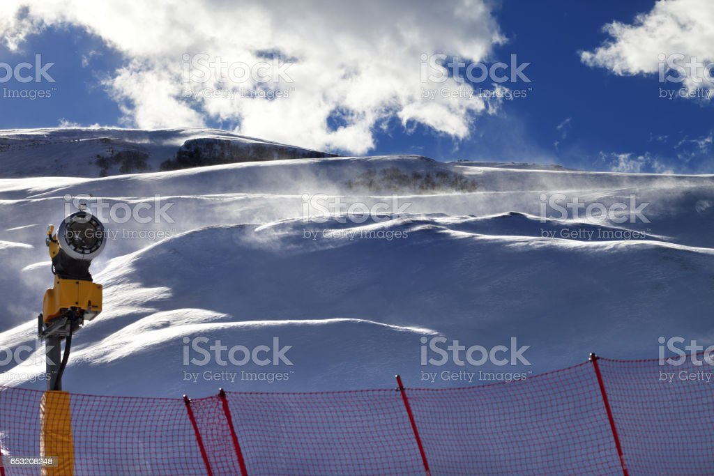 Off-piste slope during blizzard and sunlight blue sky with clouds stock photo
