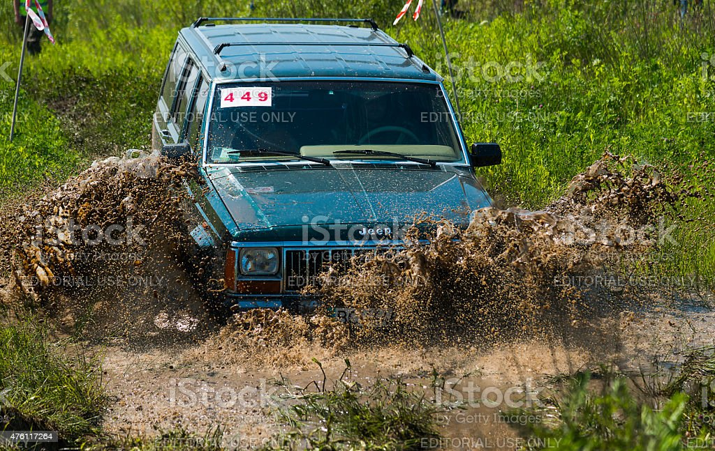 Off-road vehicle brand Jeep Cherokee overcomes a pit of mud stock photo