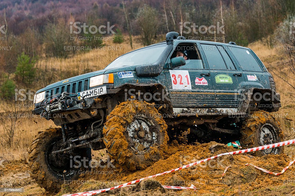 Off-road vehicle brand Jeep Cherokee overcomes a track stock photo