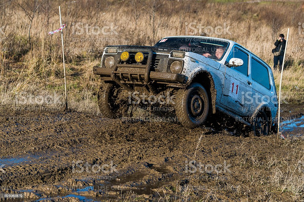 Off-road vehicle brand VAZ-NIVA overcomes the track on a polygon stock photo