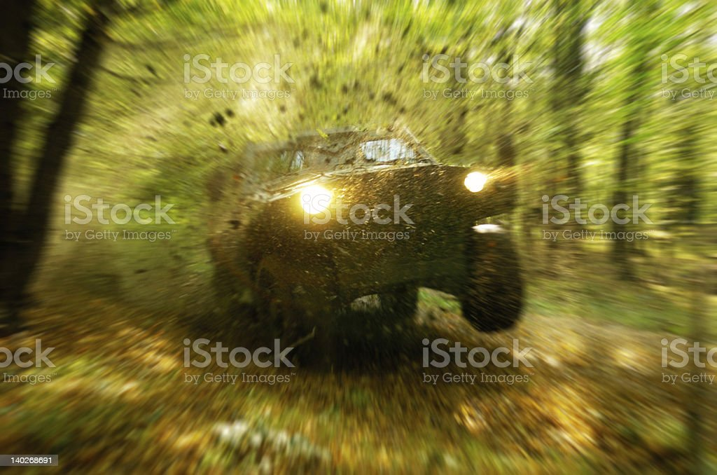 Off-road vehicle catches air in a heavily wooded area stock photo