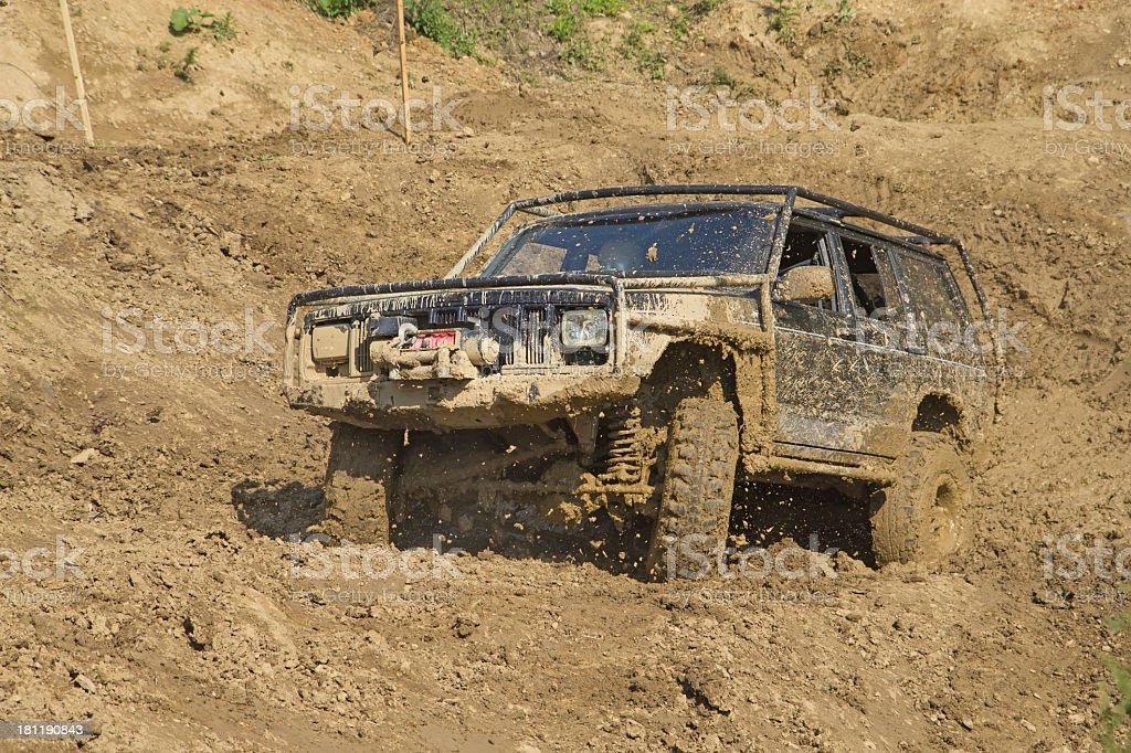 Off-road vehicle in muddy terrain. All potential trademarks are...