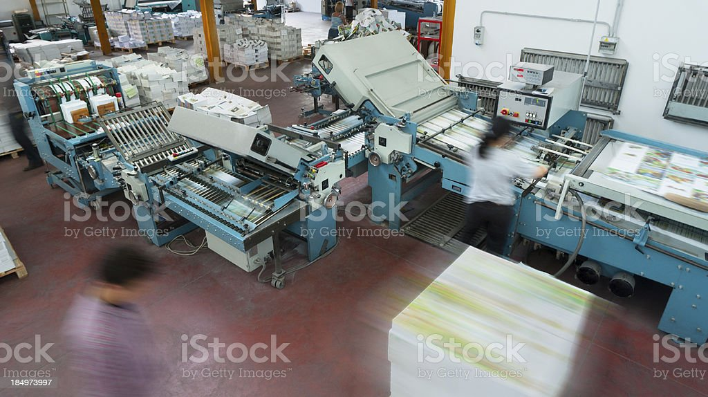 Offset printing machines at work, reams of paper on background stock photo