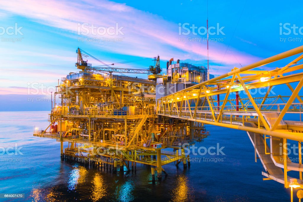 Offshore construction platform for production oil and gas with bridge in evening time stock photo