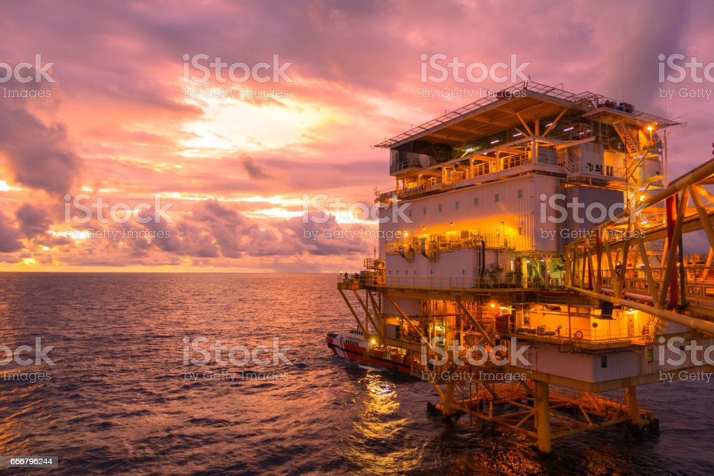 Offshore construction platform living quarter for production oil and gas with bridge in evening time stock photo