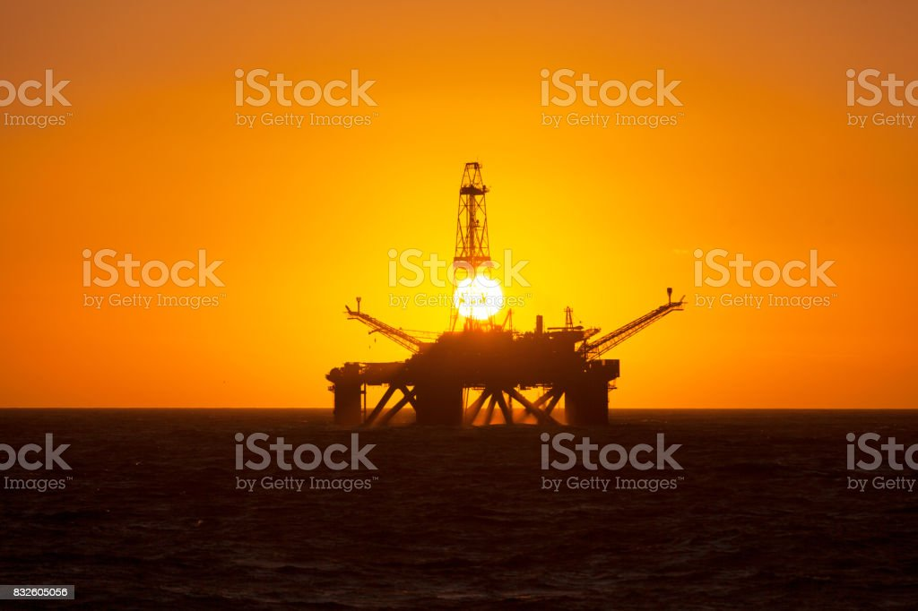 Offshore installation in the middle of the ocean at sunset time stock photo