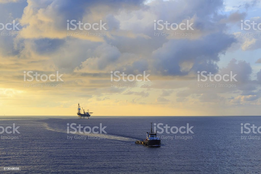 Offshore jack up drilling rig and supply boat stock photo
