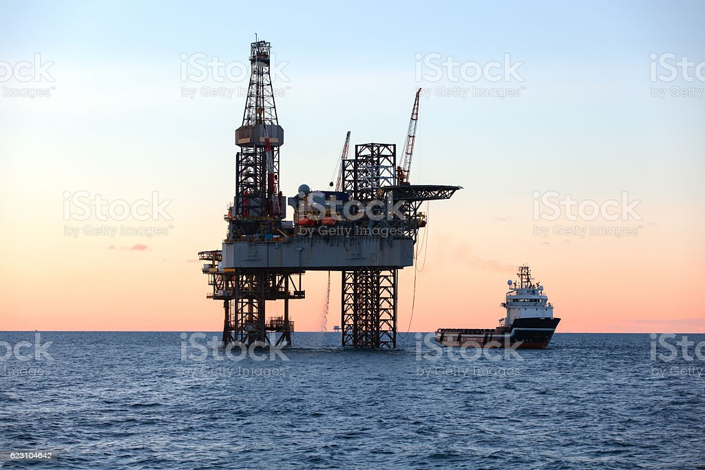 Offshore Jack Up Rig and supply ship stock photo