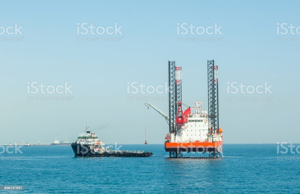 Offshore jack-up barge and supply vessel stock photo