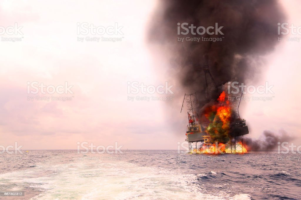 Offshore oil and rig construction damaged because worst case or fire case which can't control situation. Oil spill into the sea because incorrect of operation and accident in job out of safety rule. stock photo