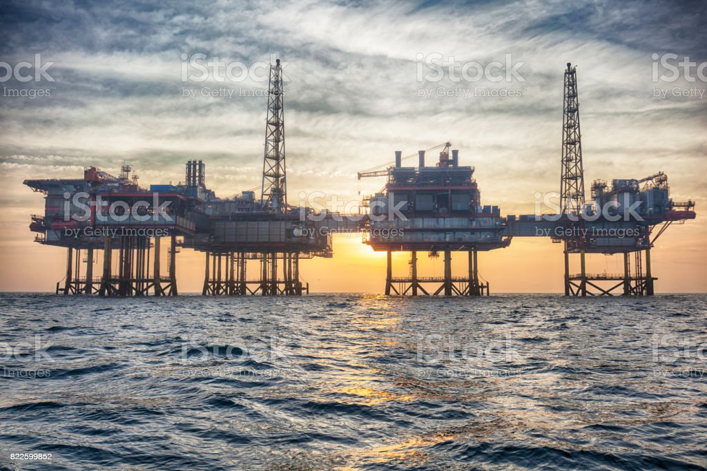 Offshore oil platform at sunset stock photo