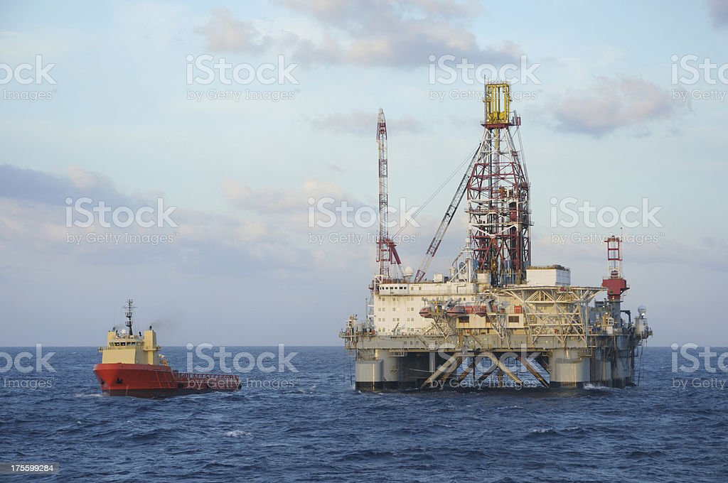 Semi-submersible oil drilling rig with supply vessel at sea.