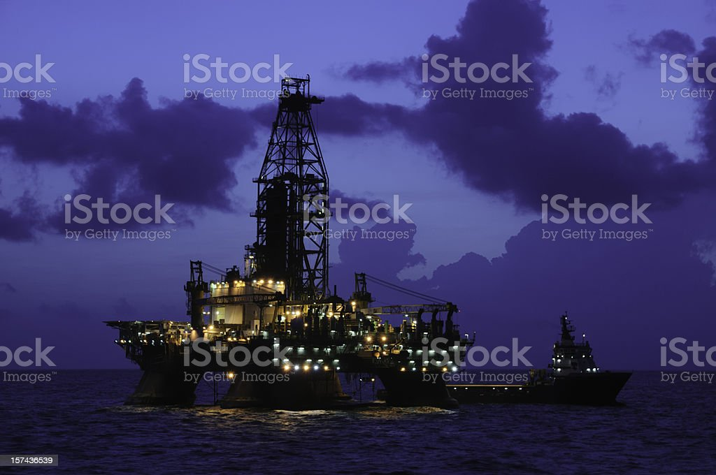 Offshore oil rig at night with supply boat stock photo