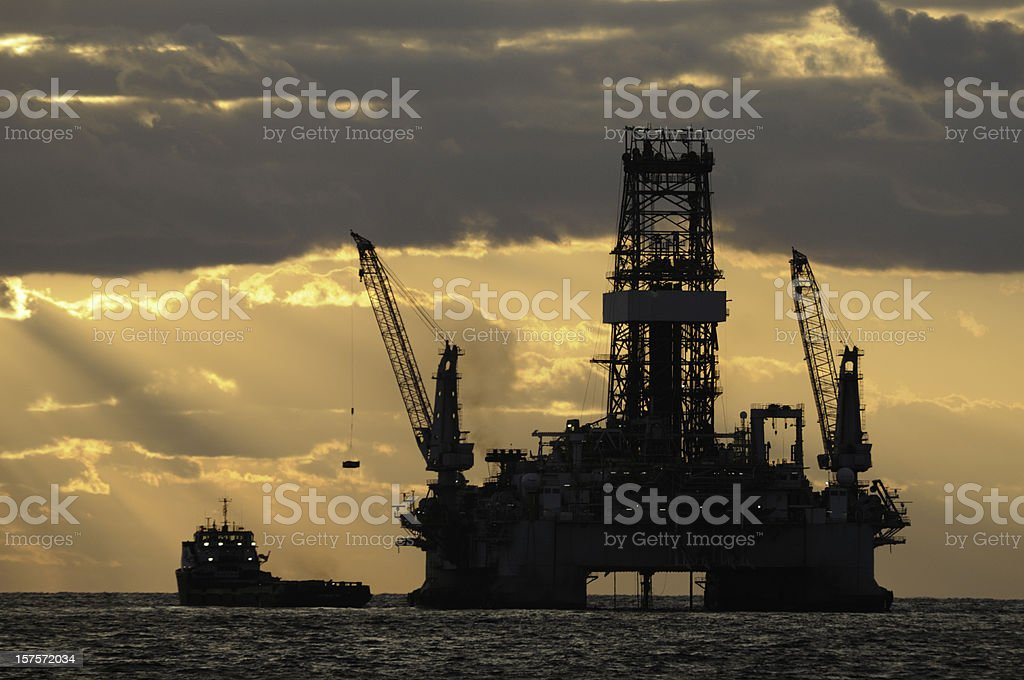 Offshore oil rig with sun and supply vessel stock photo