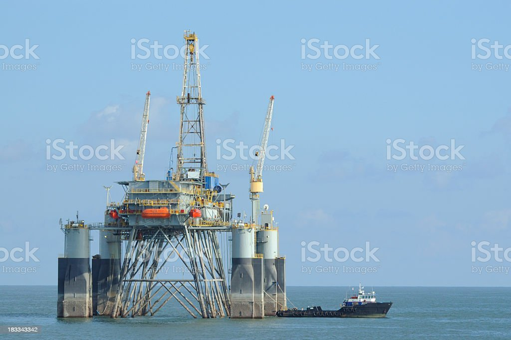 Offshore oil rig with supply vessel royalty-free stock photo