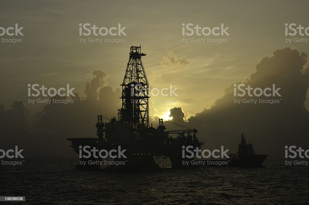 Offshore oil rig with vessel at sunrise stock photo