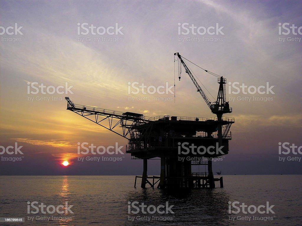 Offshore petroleum platform with sun on the horizon stock photo