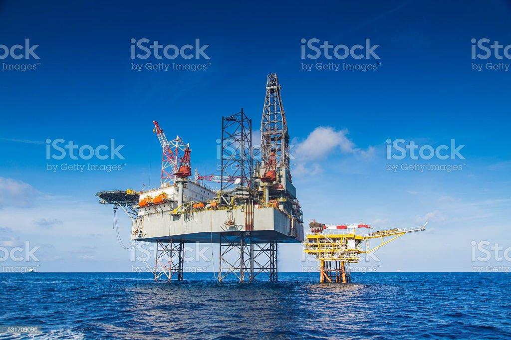 Oil and gas drilling rig work over remote wellhead platform stock photo