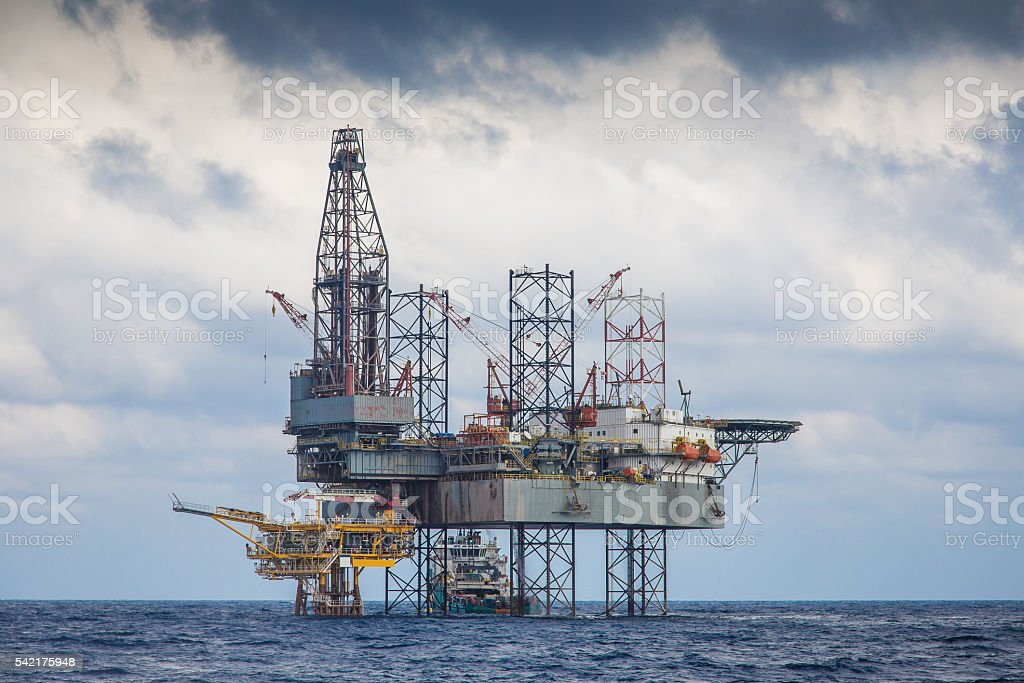 Oil and gas drilling rig working on remote wellhead platform stock photo