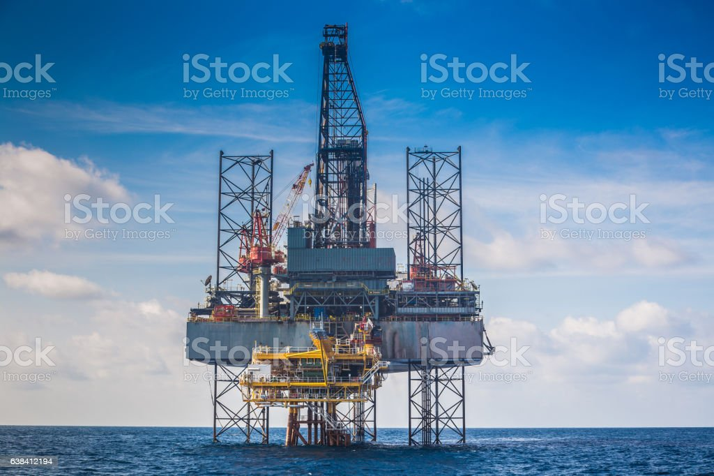 Oil and gas drilling rig working on wellhead remote platform stock photo