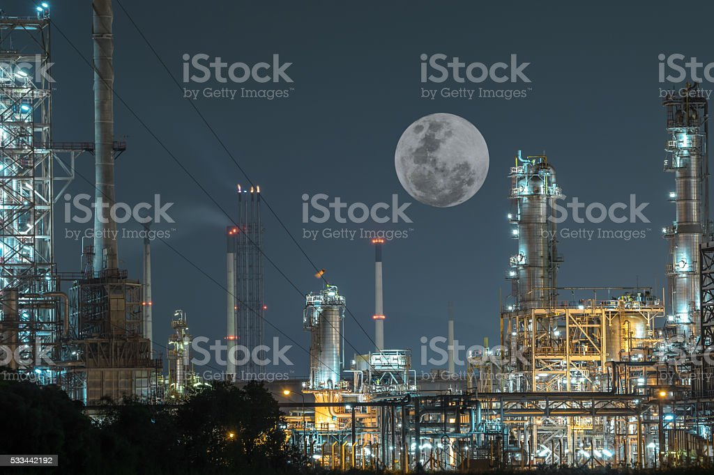 Oil and gas refinery plant under a large full moon stock photo