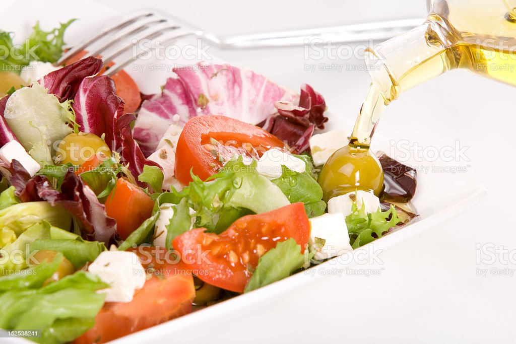 Oil based dressing pouring on a healthy colorful salad stock photo