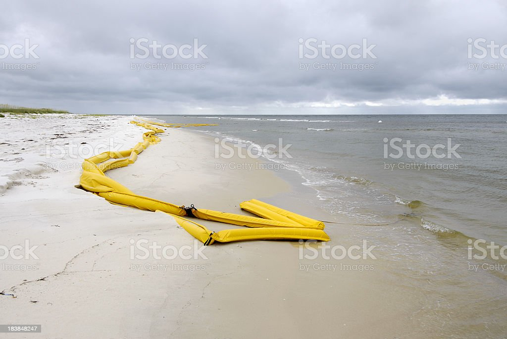 Oil boom washed ashore on sandy beach royalty-free stock photo